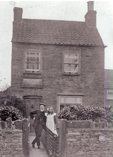 28 West St, Oldland Common, early 1900s, sign above door - Dr Harrison's Surgery - front room of private house, shows Mr W. Jefferies who became Oldland Common village postman and sister Mrs Mary Smith (nee Jefferies)