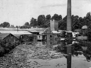 When timber offcuts replaced baled wood fibre sheets the offcuts were soaked in the pond to facilitate chipping and pulping.  The offcuts were lifted out on a conveyor on the right under the apex centre of picture. The timber was pulled toward the conveyor due to water being drawn from under the conveyor and pumped to the water tower, for the pulping process.  A floating net (centre right) contained the timber.